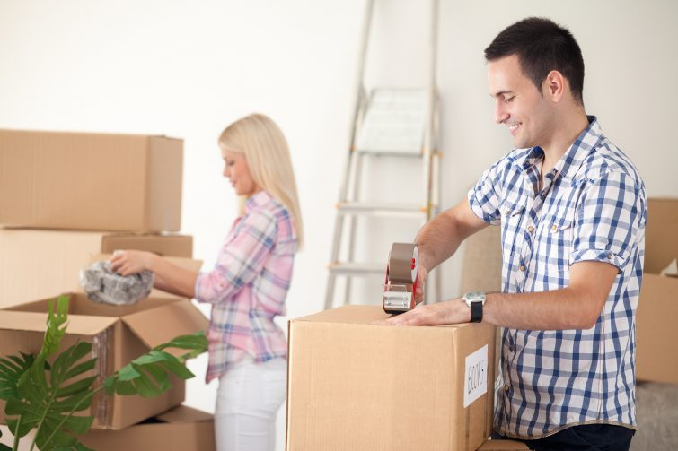 Umzugskartons packen _ young couple packing moving boxes, ready for move out