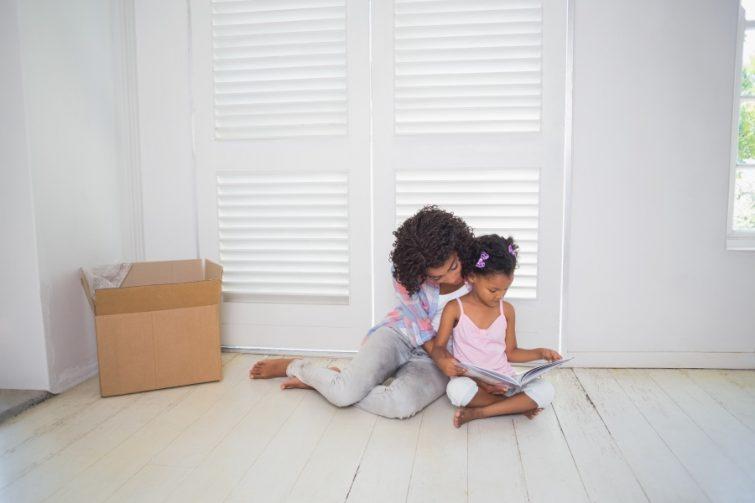 Mutter und Kind lesen ein Kinderbuch zum Umzug